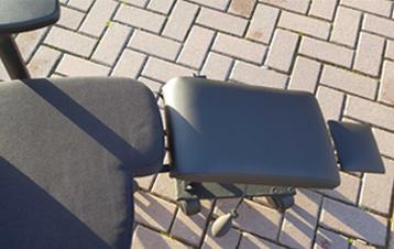 Een aangepaste bureaustoel met beensteun die op rolletjes loopt!