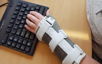 Met aangepaste muis en toetsenbord toch aan het werk ondanks twee pols braces